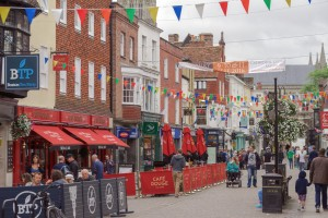 Salisbury, UK - September 4th 2016: Tourists and shoppers are walking through Salisbury City centre on a Sunday afternoon. Some are sitting down enjoying refreshments and food at tables in the street.