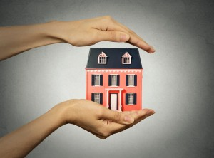 Portrait woman hands presenting small model of house, isolated grey wall background. Real estate, mortgage, home ownership concept. Safety, strong family idea. Insurance, protection