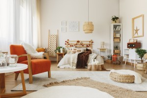 Fully furnished Scandinavian bedroom with a lot of rugs, chair, small table, and vintage radio