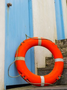 Single life buoy or ring leaning on wooden blue door